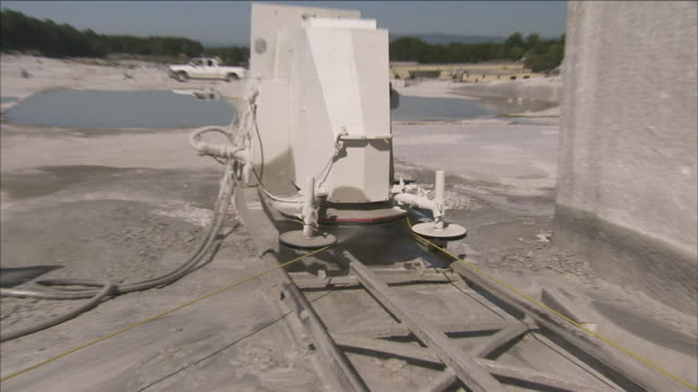 water sprays on a large piece of mining equipment in a granite quarry. - granite rock stock videos & royalty-free footage