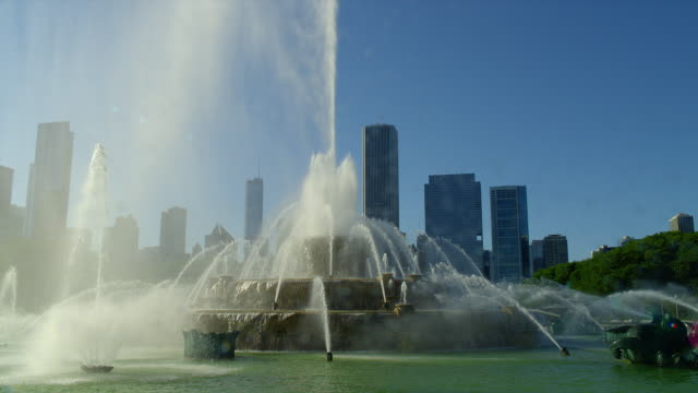 water sprays up in buckingham fountain in grant park in front of the chicago, illinois skyline. - buckingham fountain stock videos & royalty-free footage