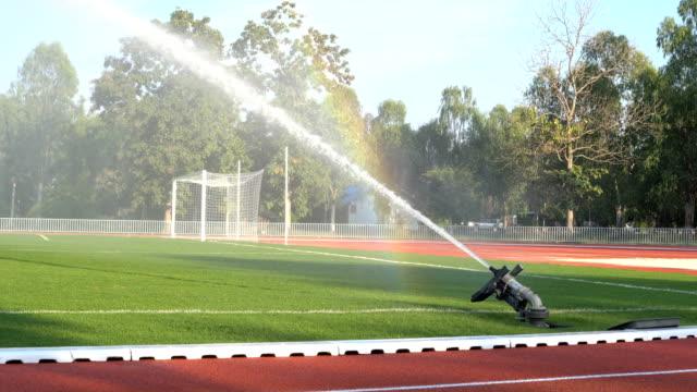 vídeos de stock, filmes e b-roll de aspersor de água ms 4k o futebol de campo grama verde. - campo de futebol