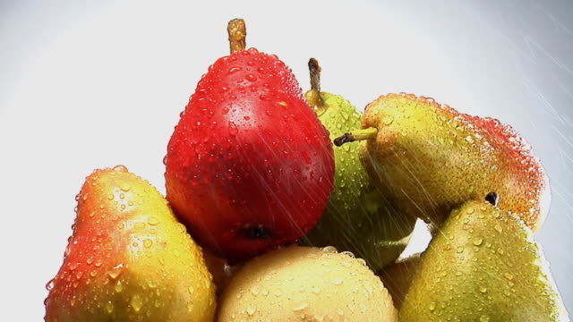 cu, water sprinkling on stack of rotating red, green and yellow pears - pear stock videos & royalty-free footage