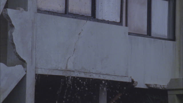 Water spurts from a damaged, flooded building.