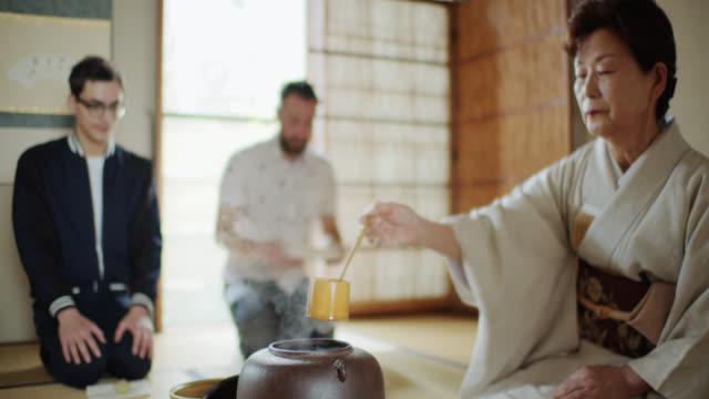 vídeos de stock, filmes e b-roll de água cozinhando na cerimónia japonesa tradicional do chá atendida por dois homens - washitsu