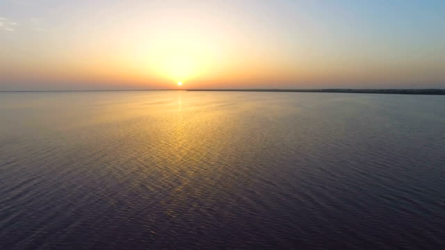 Water surface in golden glow of sunset, aerial video