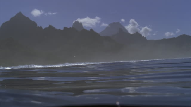 vídeos de stock, filmes e b-roll de slo mo cu water surface with rugged island in background / moorea, tahiti, french polynesia - polinésia francesa