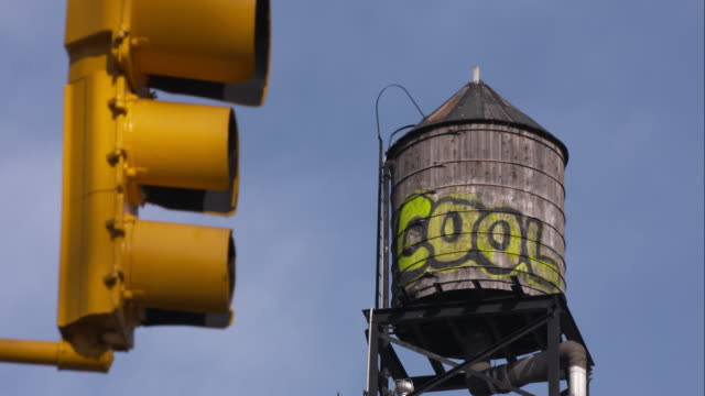 a water tank with graffiti on the side and a traffic signal - capital letter stock videos & royalty-free footage