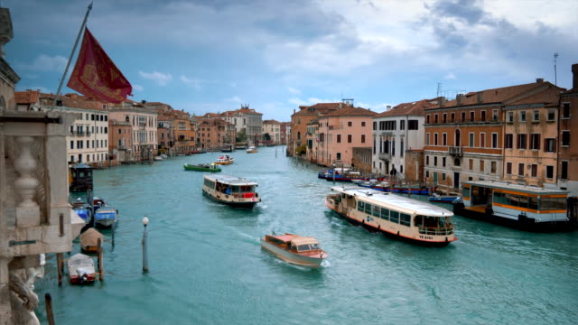 water taxi and vaporetto boats traverse the grand canal in venice, italy - barca a motore video stock e b–roll