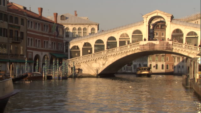 a water taxi docks near the rialto bridge on the grand canal. - water taxi stock videos & royalty-free footage