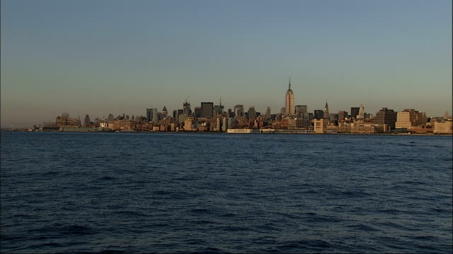 A water taxi glides past Manhattan Island on the Hudson River. Available in HD.