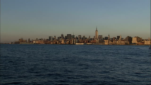A water taxi glides past Manhattan on the Hudson River. Available in HD.