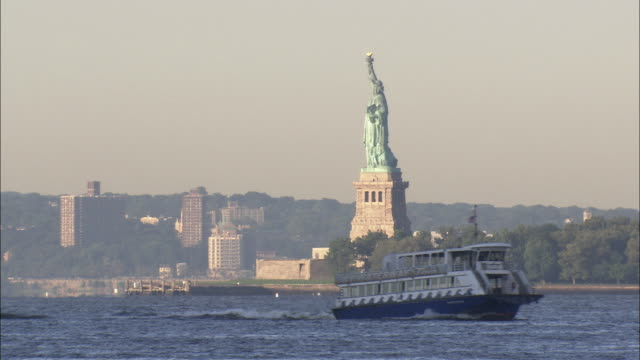 water taxi passes by the statue of liberty - フェリー船点の映像素材/bロール