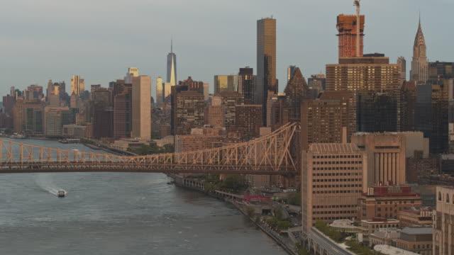 a water taxi passing under ed koch queensboro bridge. aerial drone footage with the cinematic panning and descending camera motion. - east river new york city stock videos & royalty-free footage