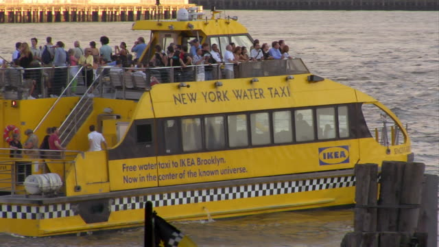 a water taxi pulls away from the dock on a river in downtown manhattan. - water taxi stock videos & royalty-free footage