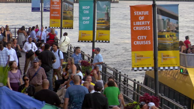 a water taxi sits next to a crowded dock in downtown manhattan. - ferry stock videos and b-roll footage