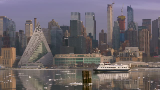 water taxi slowly moves along the cold hudson river waters passing by the west side skyline on an overcast day. - water taxi stock videos & royalty-free footage