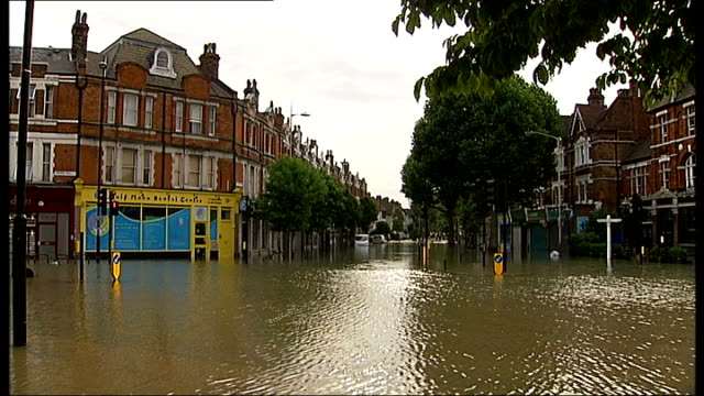 thames water want to impose customer surcharge to cover debts lib herne hill gv flooded road man wading through water - herne hill stock videos & royalty-free footage