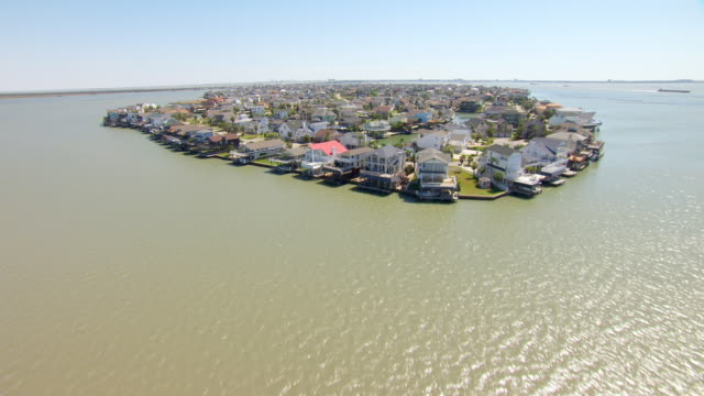 vidéos et rushes de ms aerial la water to over housing development in gulf coast and galveston bay / tiki island, texas, united states - gulf coast states