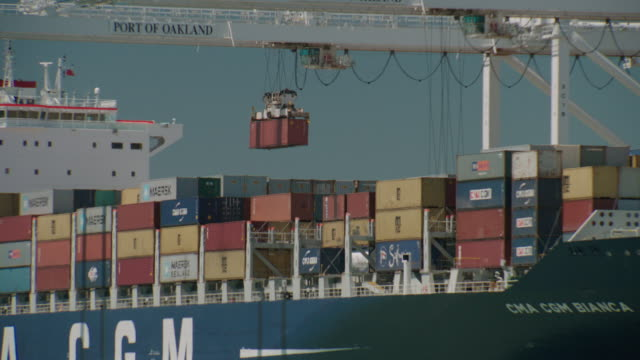 water to stacks of freight crates on ship w/ cgm lettering, crane moving one container. industry, industrial, harbor. - トリビューンタワー点の映像素材/bロール