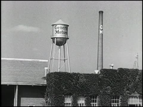 vídeos de stock e filmes b-roll de ws water tower and smoke stack rises above ivycovered buildings at gm milford proving grounds xws pan across proving grounds acreage 1949 general... - general motors