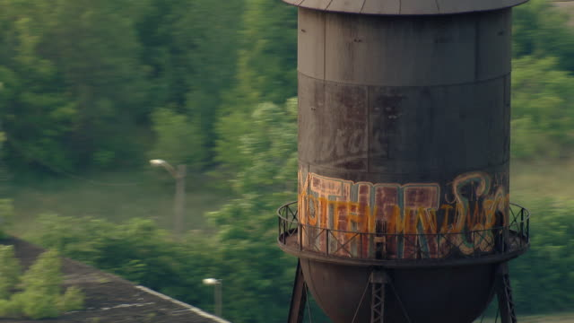 water tower at detroit's packard automotive plant, marked with graffiti. - rusty stock videos & royalty-free footage