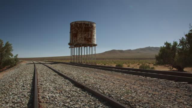 water tower train tracks in the desert. - schienenverkehr stock-videos und b-roll-filmmaterial
