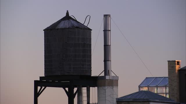 vídeos de stock, filmes e b-roll de water towers hold a water supply for a new york city neighborhood. - tanque de armazenamento