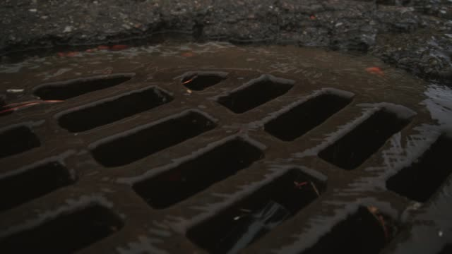 water trickles into a round grated sewer drain - concrete stock videos & royalty-free footage