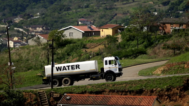 ms slo mo water truck driving up hill in rural township/ kwazulu-natal/ south africa - water conservation stock videos & royalty-free footage