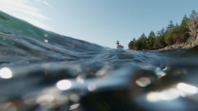 vidéos et rushes de l'eau lave au-dessus de la caméra dans le port de vendredi avec le phare de four de chaux dans le fond près de l'île de san juan sur une journée ensoleillée - vue du sol