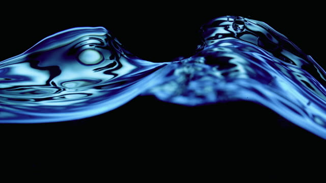 water wave and buubles lit in luminescent blue in a tank, black background - 水平アングル点の映像素材/bロール