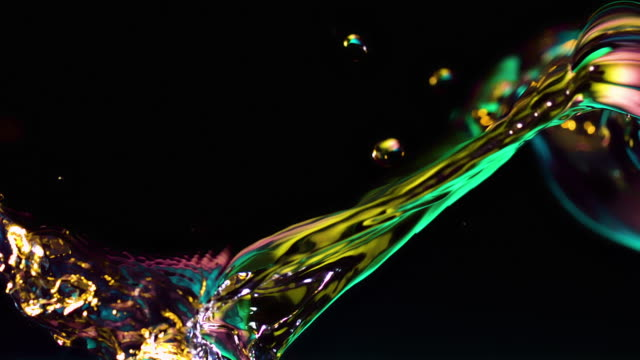 water wave and buubles lit in luminescent colors in a tank, black background, slow motion - makrofotografie stock-videos und b-roll-filmmaterial