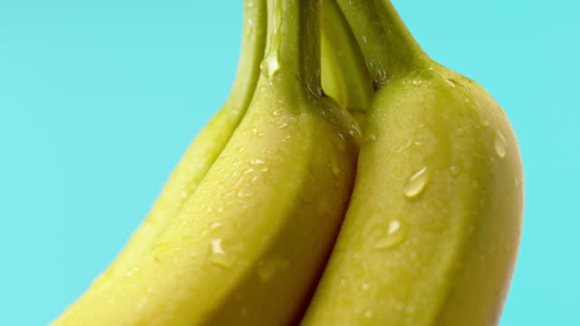 slo mo a waterdrop gliding down a banana - small group of objects stock videos & royalty-free footage