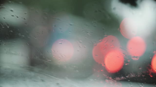 Waterdrops in car glass with traffic out of focus