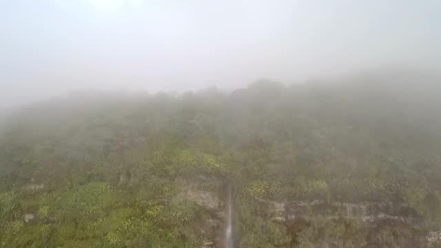 Waterfall Behind Thick Cloud and Tropical Rainforest, Aerial, Revealed Going Up