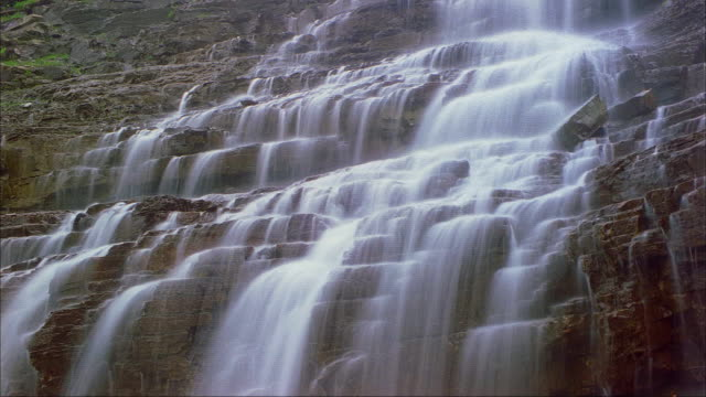 A waterfall cascades down a rocky cliff in Glacier National Park.