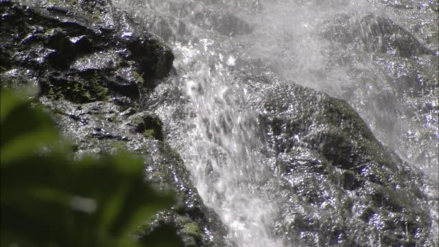 a waterfall cascades down a rugged cliff. - waterfall点の映像素材/bロール