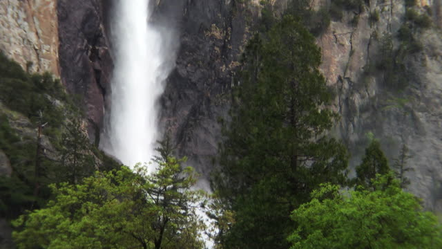 a waterfall crashes over a cliff in yosemite national park. - igneous stock videos & royalty-free footage