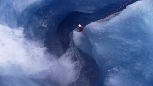 a waterfall crashes past an ice climber who rappels into a crevasse. - abseiling stock videos & royalty-free footage