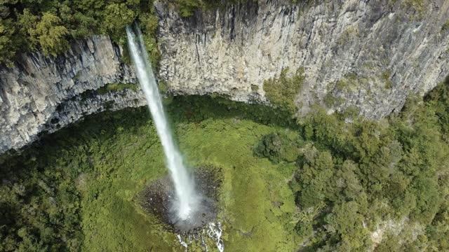 vídeos de stock, filmes e b-roll de cachoeira caindo do topo de um penhasco de coluna de basalto - paredão rochoso