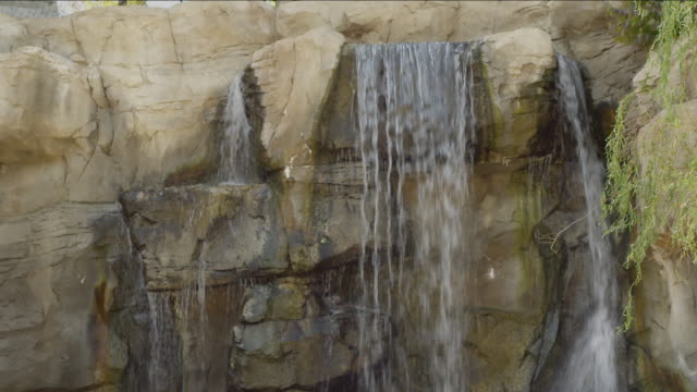 Waterfall feature in an enclosure for zoo animals.