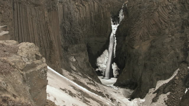 a waterfall flows down a basalt rock face in northern iceland. - basalt stock videos & royalty-free footage
