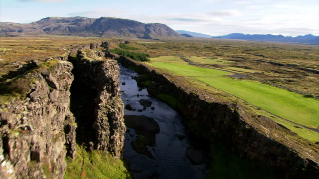vidéos et rushes de a waterfall flows into a long valley created by the continental drift in iceland. available in hd. - géologie