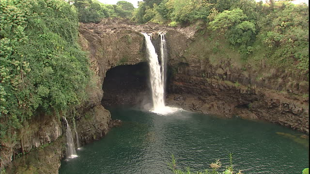 A waterfall flows over the mouth of a cave in Hilo, Hawaii.