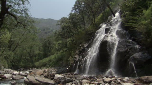 Waterfall gushes from verdant hills into valley Available in HD.