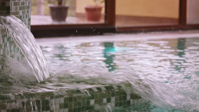 waterfall in swimming pool at the spa - hot tub stock videos & royalty-free footage