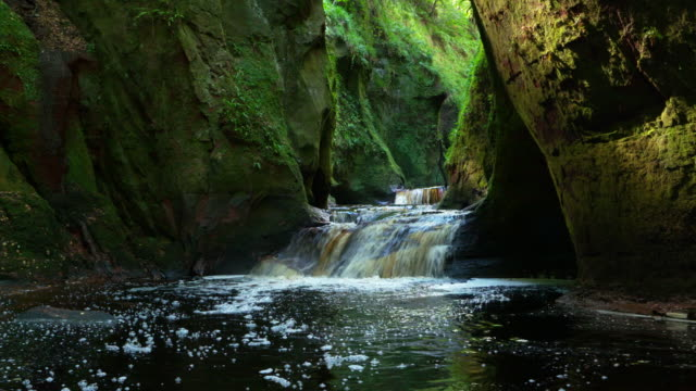 waterfall in the famous finnich glen near killearn. - スコットランド点の映像素材/bロール