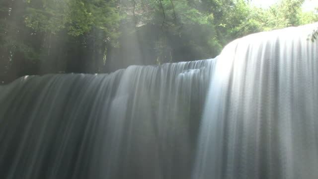 Waterfall lit by sunshine through trees