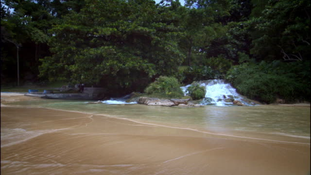ws waterfall on beach flowing into ocean waves / ocho rios, jamaica - jamaican people stock videos and b-roll footage