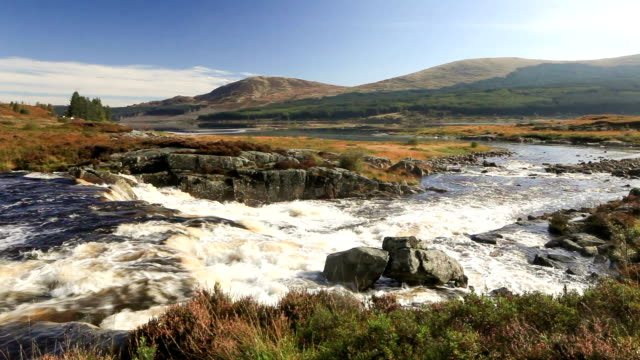 a waterfall on carrick lane river in the galloway forest park, scotland. - bacino idrico video stock e b–roll
