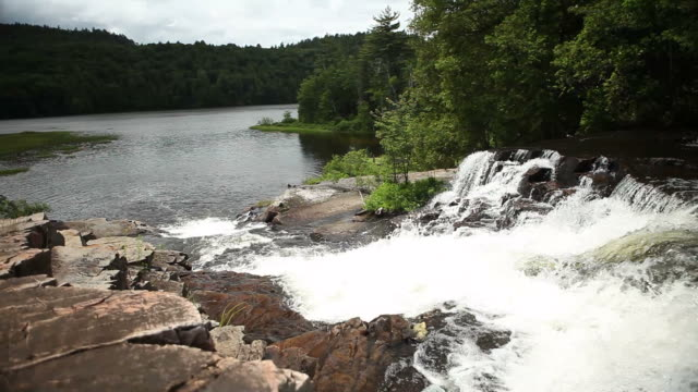 Waterfall on Edge of Quiet Lake in Canadian Wilderness