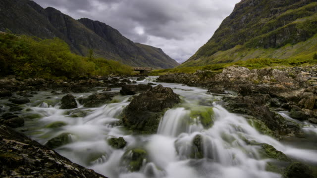 vidéos et rushes de a waterfall on the river coe flows through glencoe in the scottish highlands - vallée